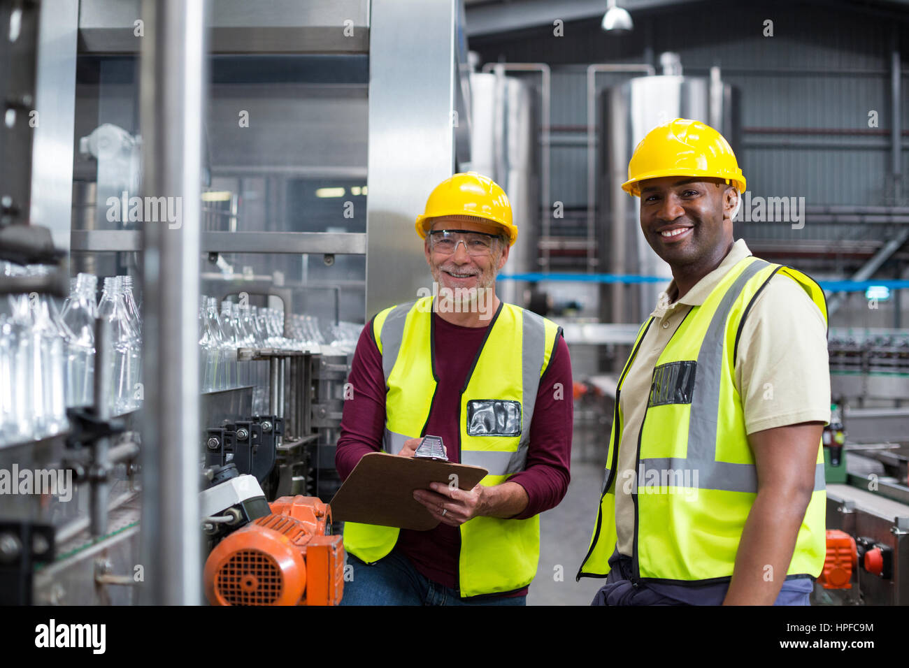Two factory workers discussing while monitoring drinks production line at factory Stock Photo