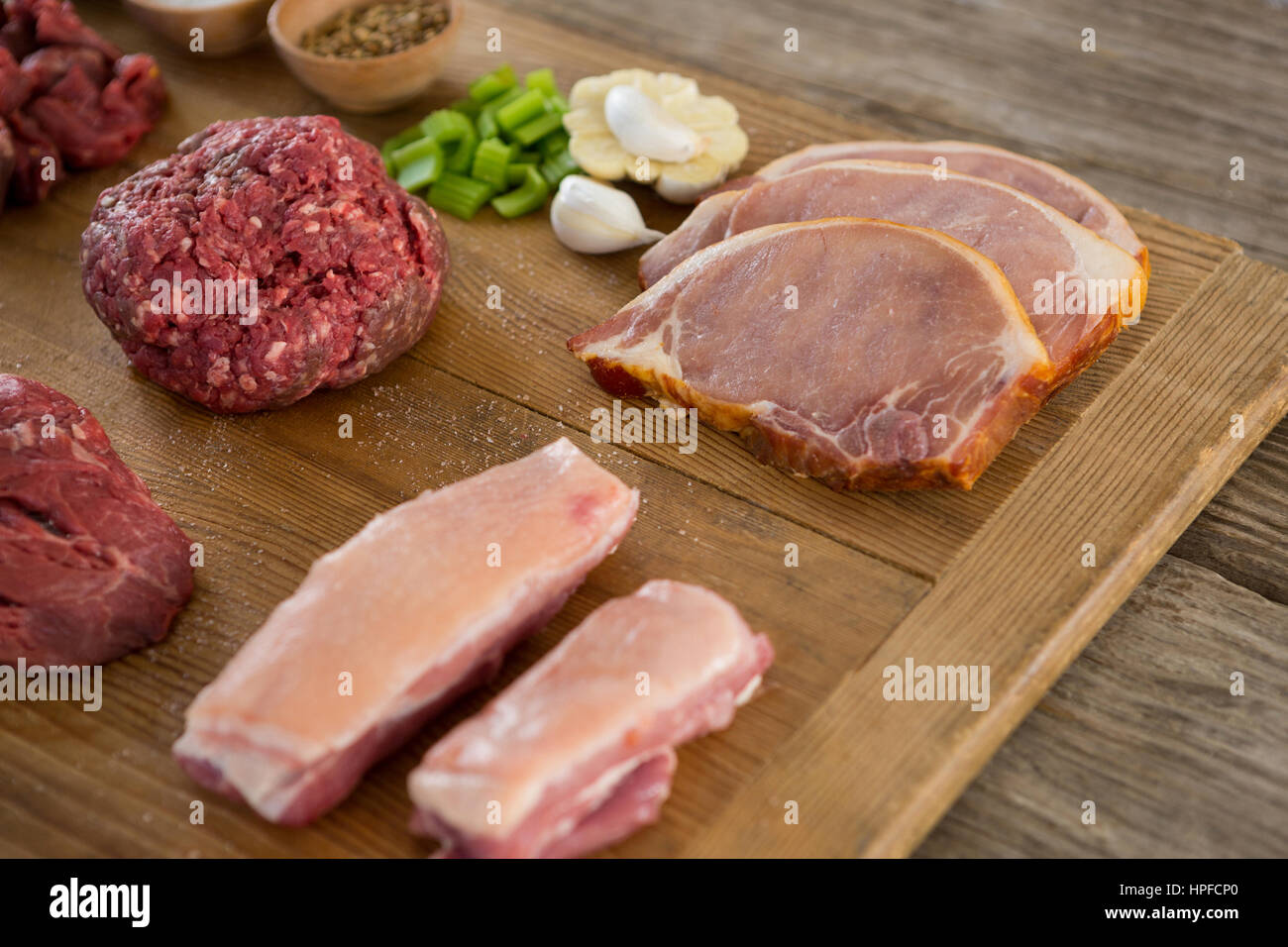 Varieties of meat and spices on wooden tray against wooden background - Stock Image