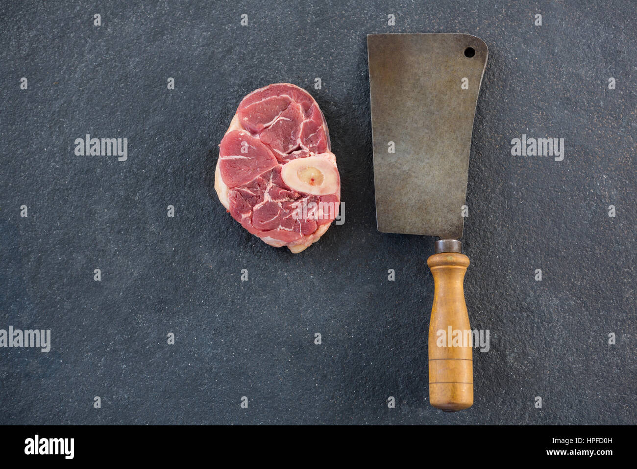Sirloin chop and cleaver against black background - Stock Image