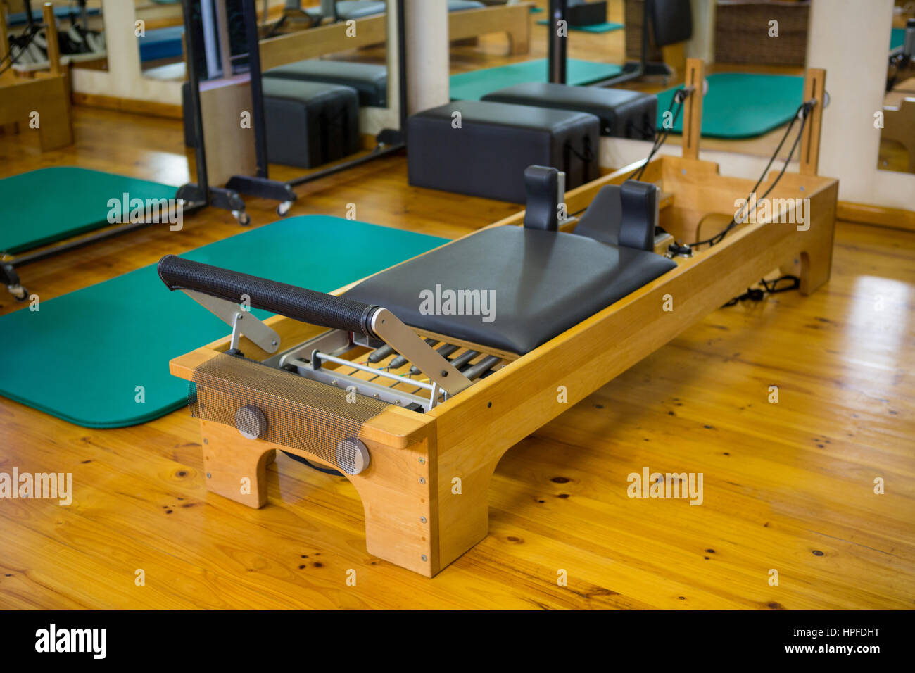 Reformer on wooden floor in gym - Stock Image