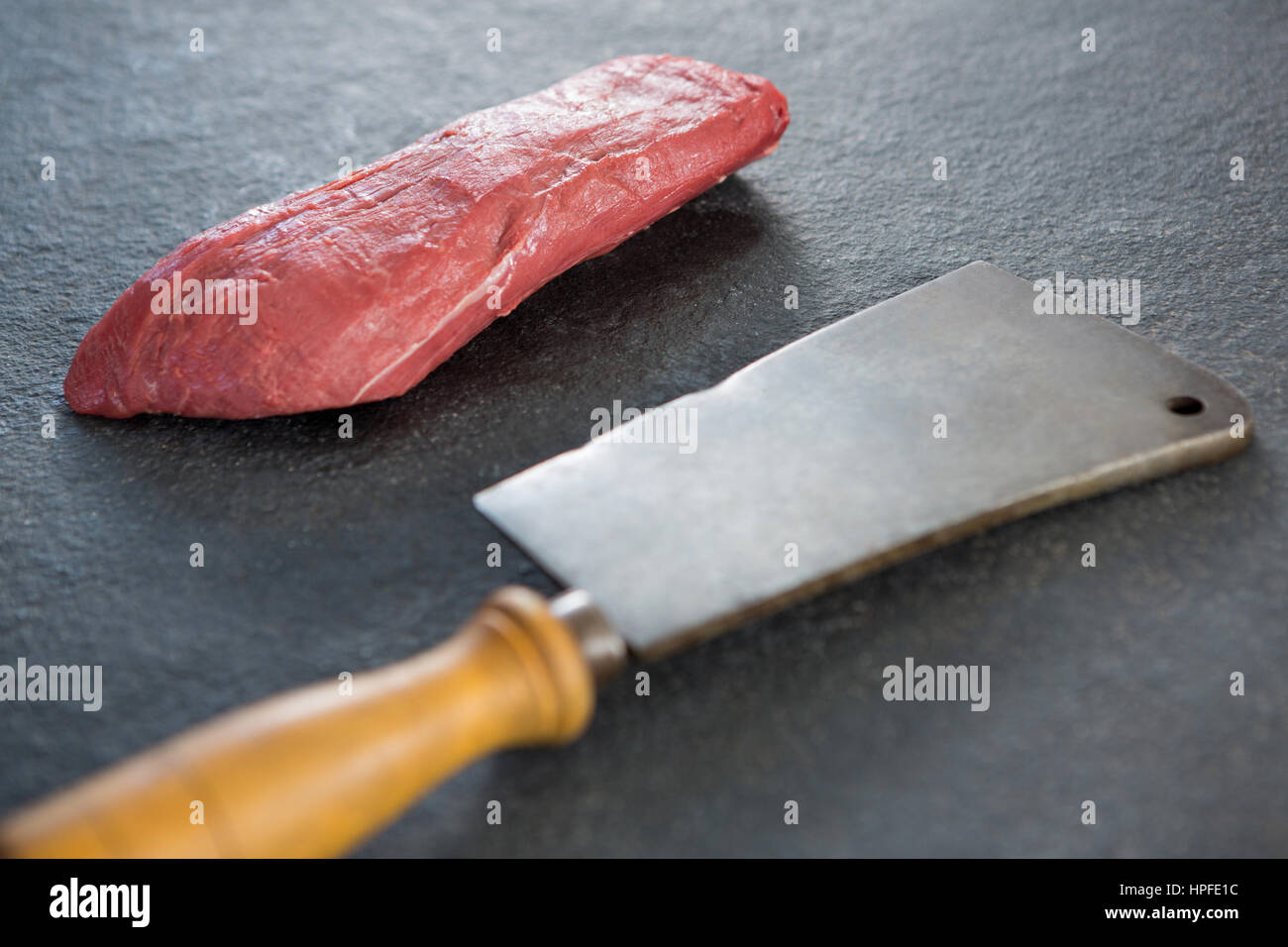 Beef steak and cleaver against black background - Stock Image