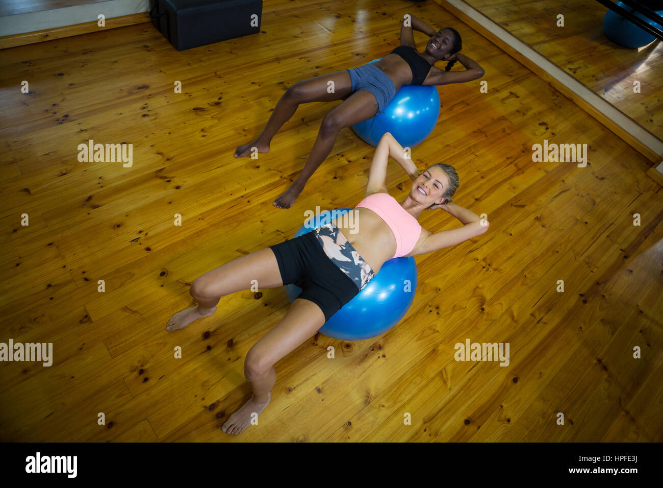 Two fit women performing pilate on exercise ball in fitness studio - Stock Image
