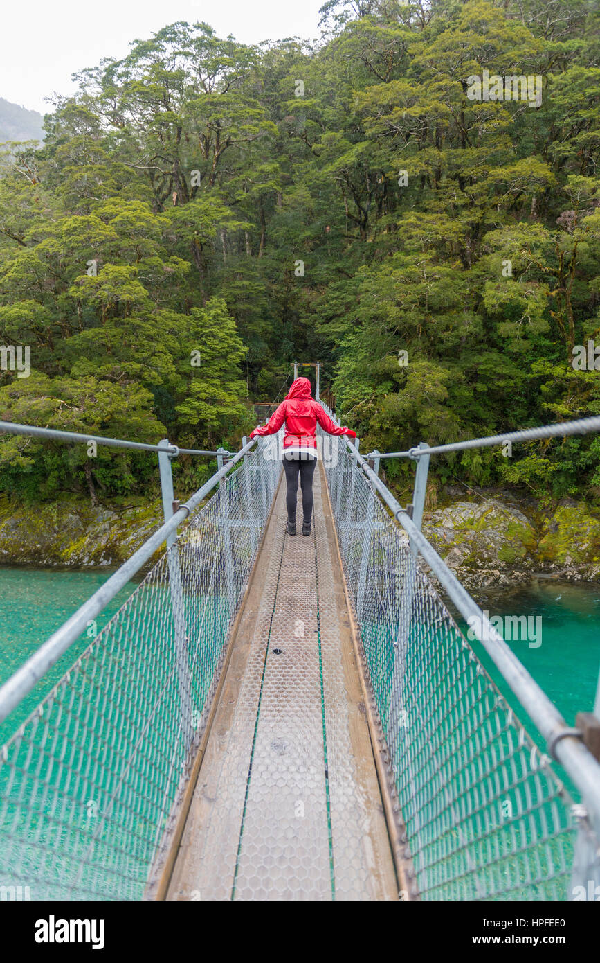 Woman crossing Suspension Bridge, Blue Pools, Haast Pass, West Coast, Southland, New Zealand - Stock Image