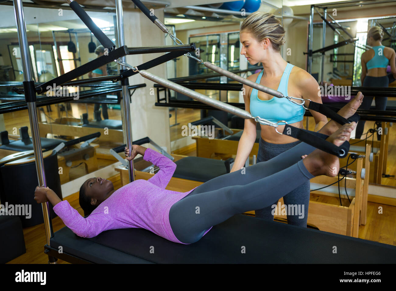 Trainer assisting woman with pilates on reformer in fitness studio - Stock Image