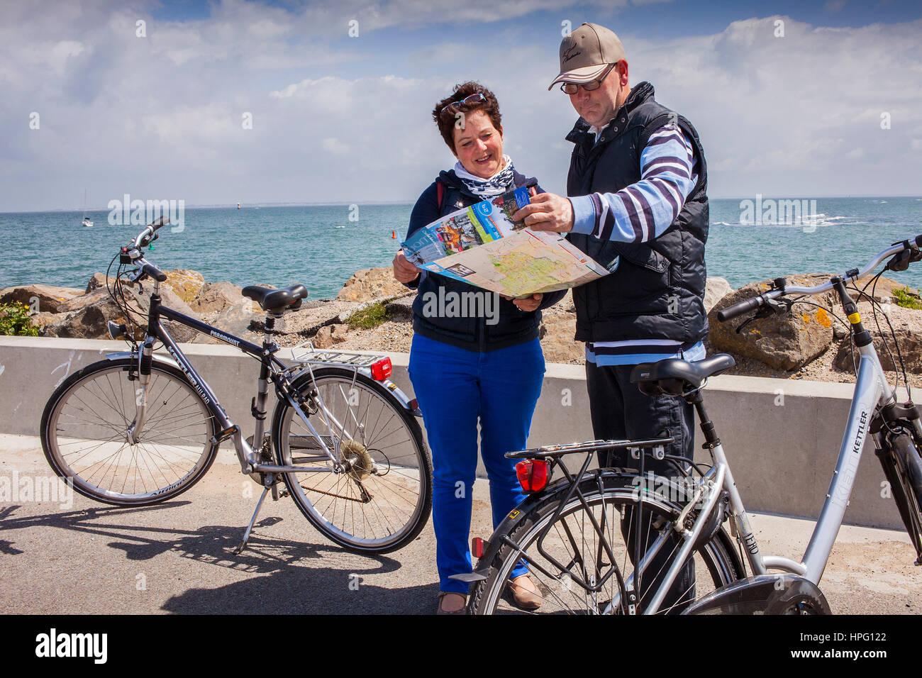 Tourists looking the map, in Port of l'Herbaudière,  Île de Noirmoutier, La Vendée, Pays de la Loire, France Stock Photo