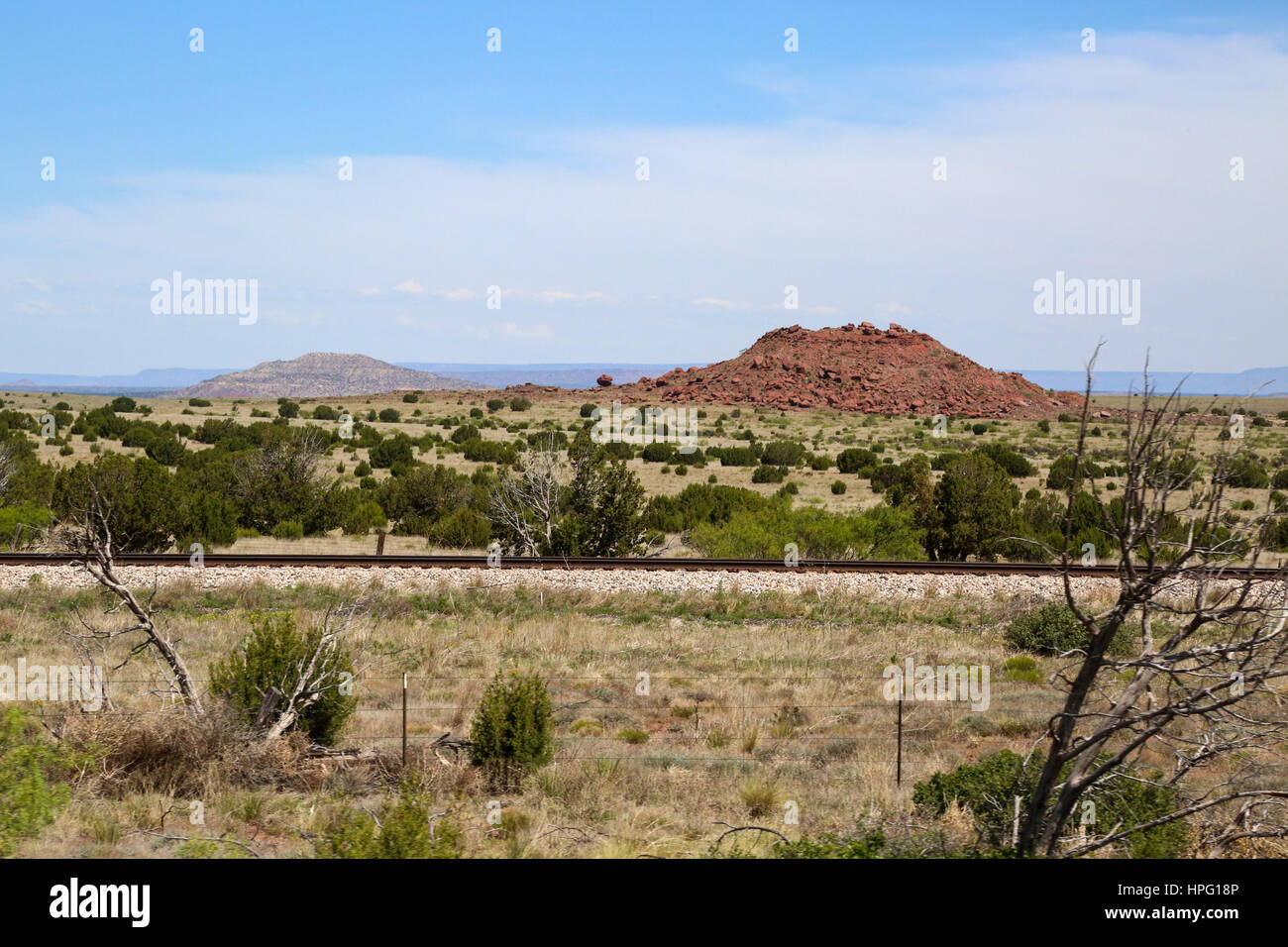 Buttes in the Distance Beyond Train Tracks in New Mexico running parallel to North Side of Interstate 40 / Rte 66 Stock Photo