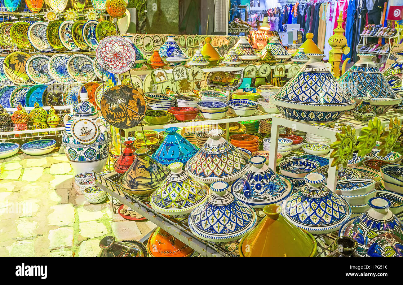 The handmade pottery with bright arabic patterns in tourist market stall, located on promenade of El Kantaoui, Tunisia. - Stock Image