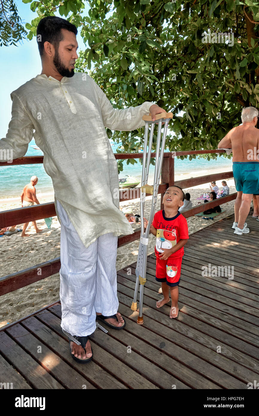 Young Asian boy intrigued by a disabled man with walking crutches. Thailand Southeast Asia - Stock Image