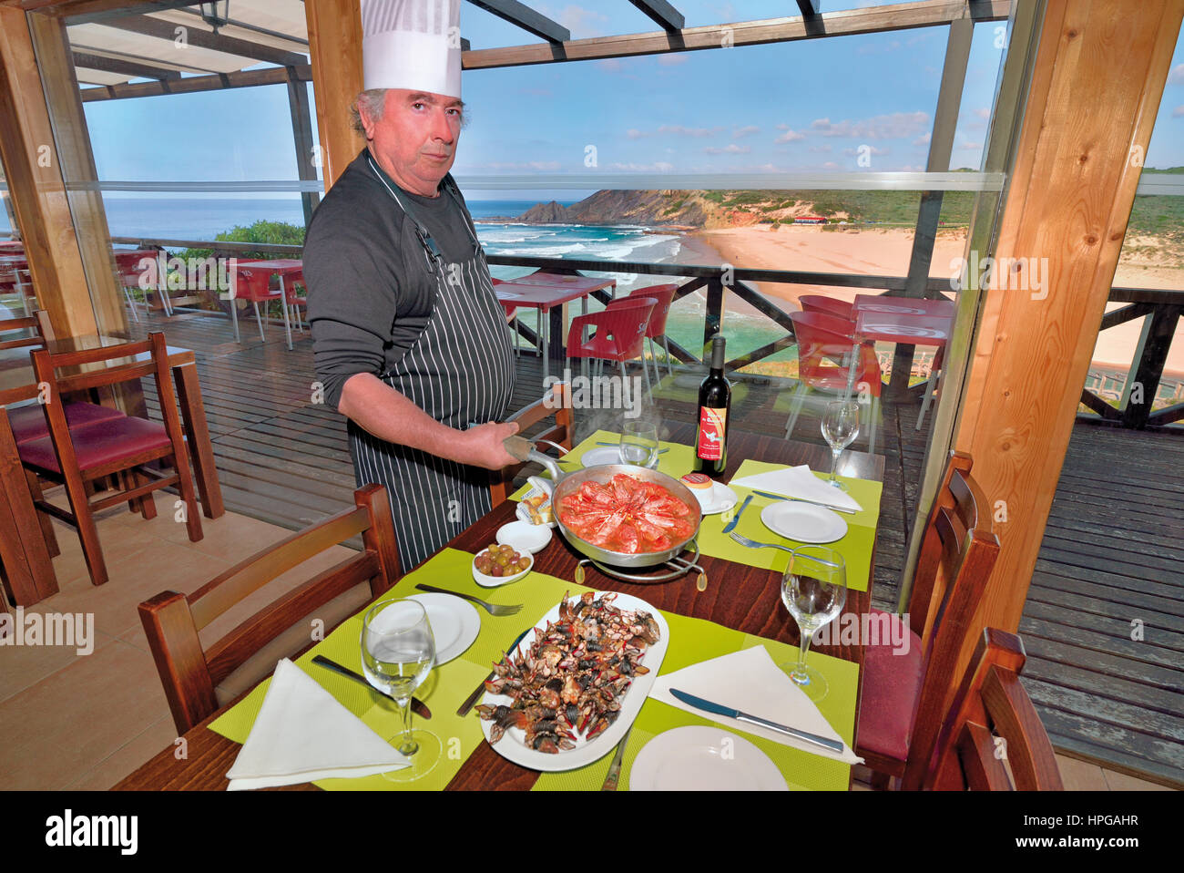 Portugal: Chef Gabriel with his house specialty posing at decored table with seaview in the restaurant Gabriel II - Stock Image
