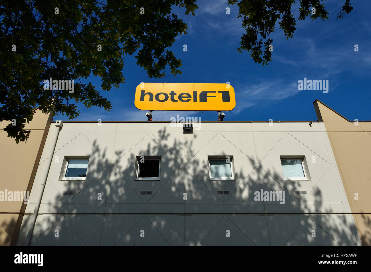 France, Formule 1 Hotel facade and its sign against a blue sky. Foliage in the foreground - Stock Image