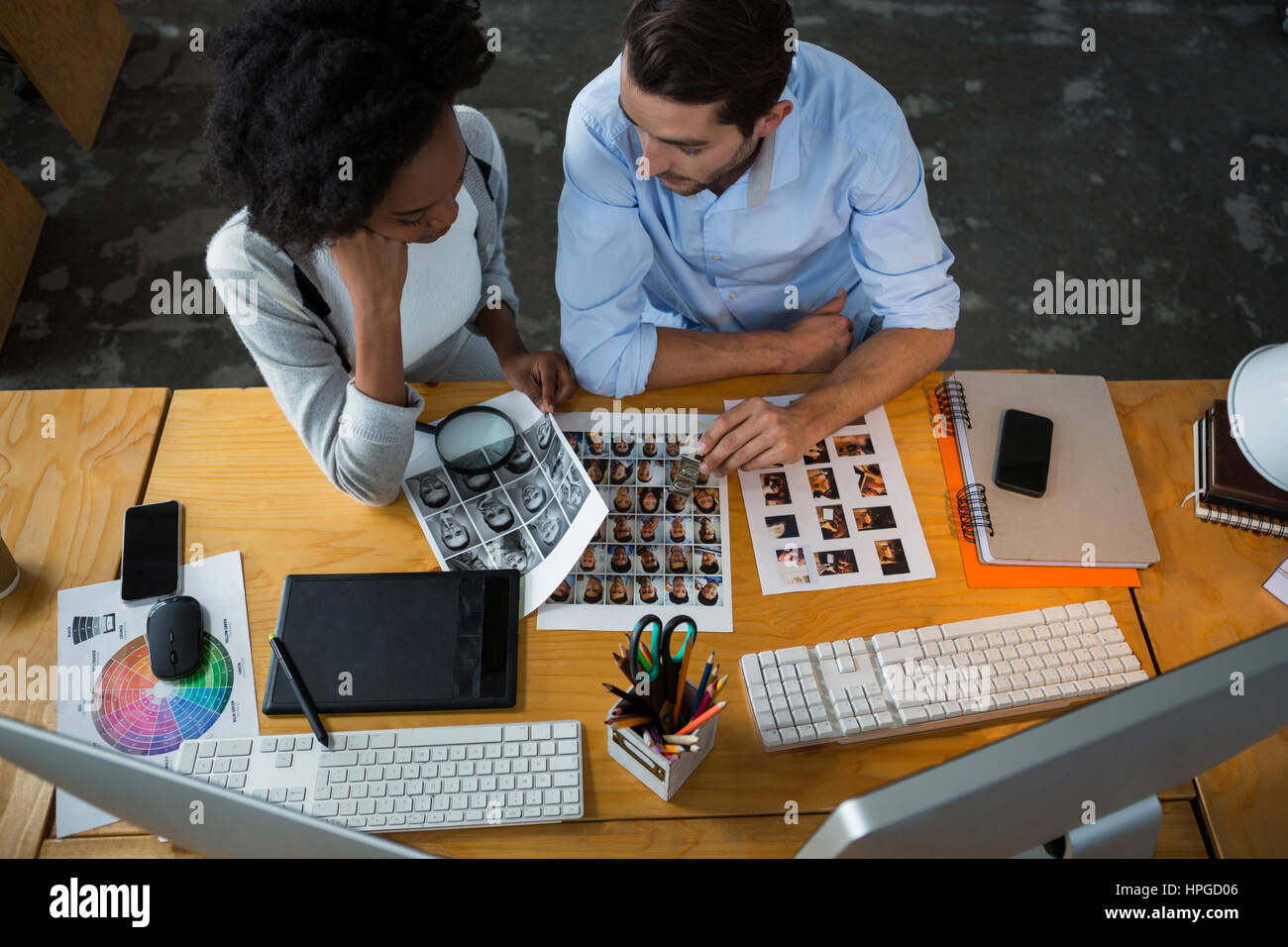 Man and woman discussing over photographs in creative office - Stock Image