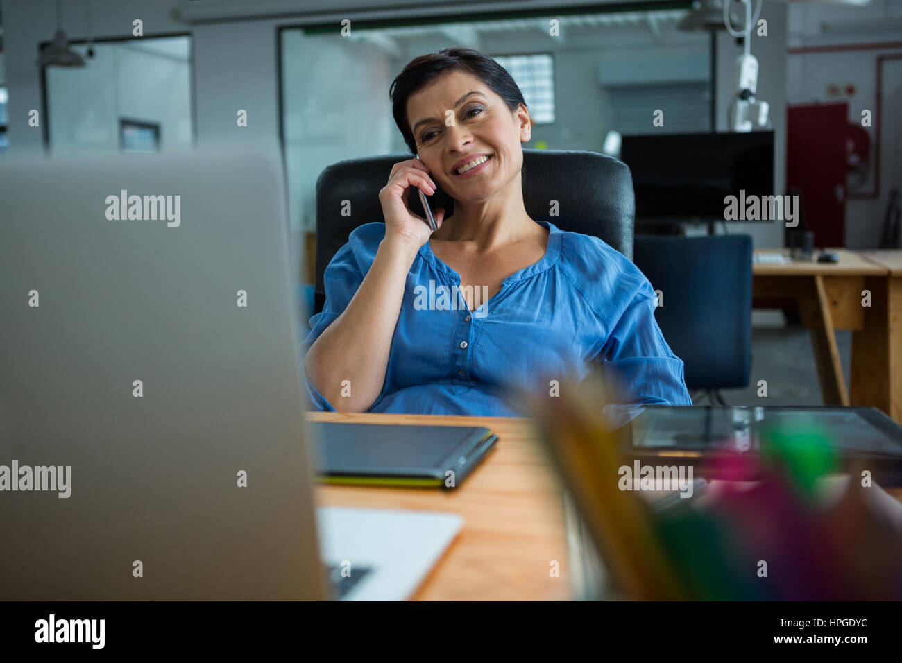 Female graphic designer talking on mobile phone in creative office - Stock Image