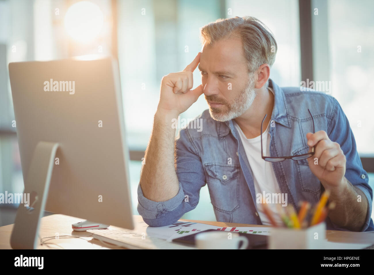 Male graphic designer working on computer in office - Stock Image