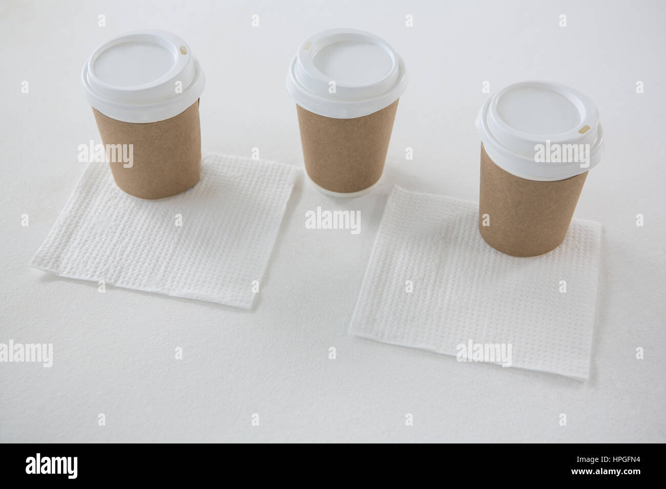 Disposable cups served with tissue papers on white background - Stock Image