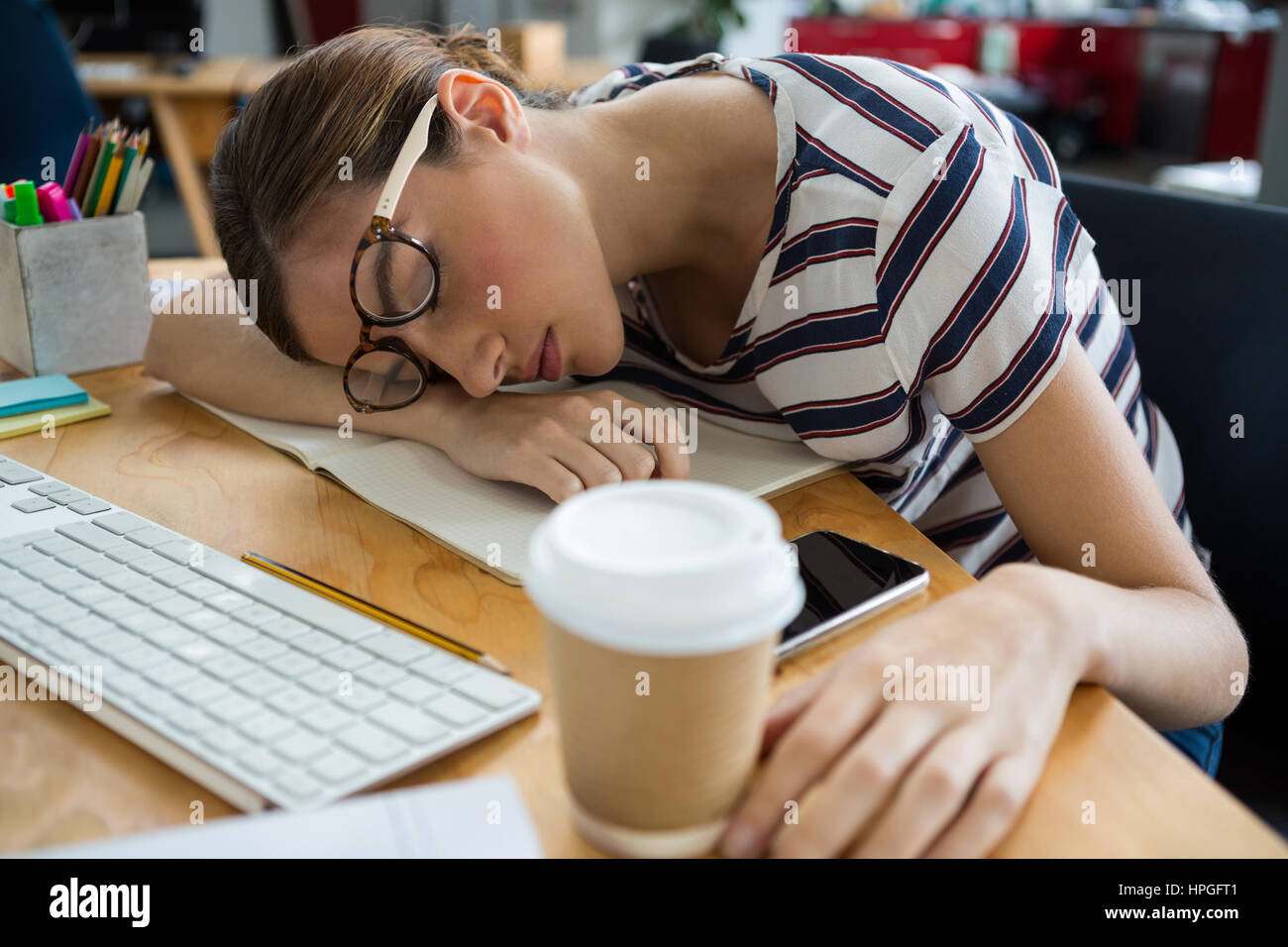 Overworked graphic designer sleeping on his desk in the creative office - Stock Image