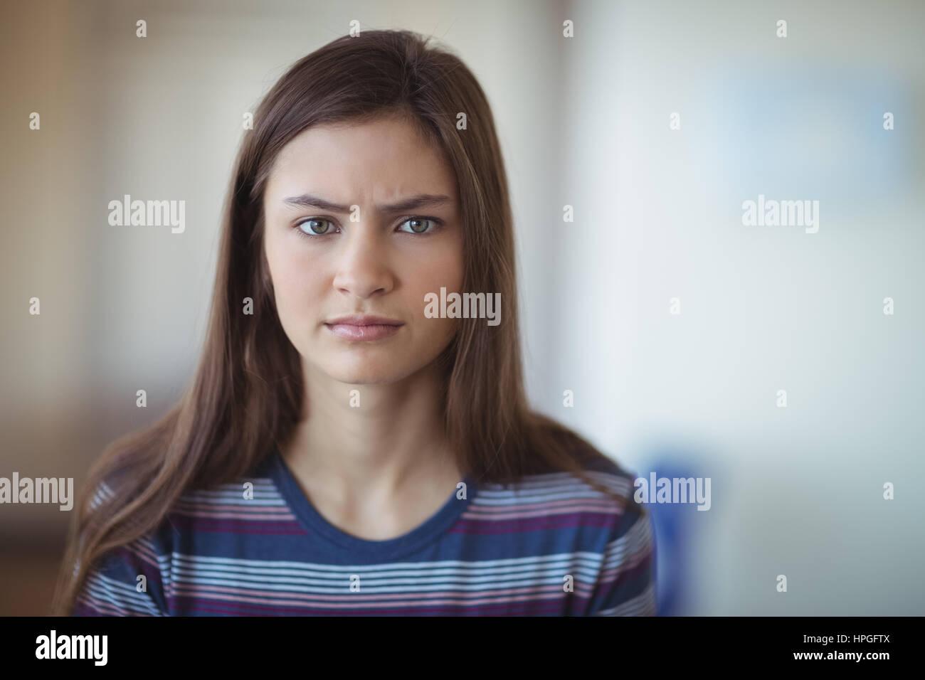 Portrait of sad schoolgirl in school - Stock Image
