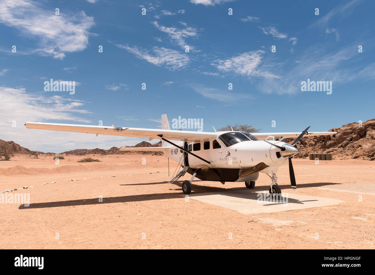 A Cessna 208 parked on the airstrip serving the Wilderness Safaris Hoanib Skeleton Coast Camp. - Stock Image