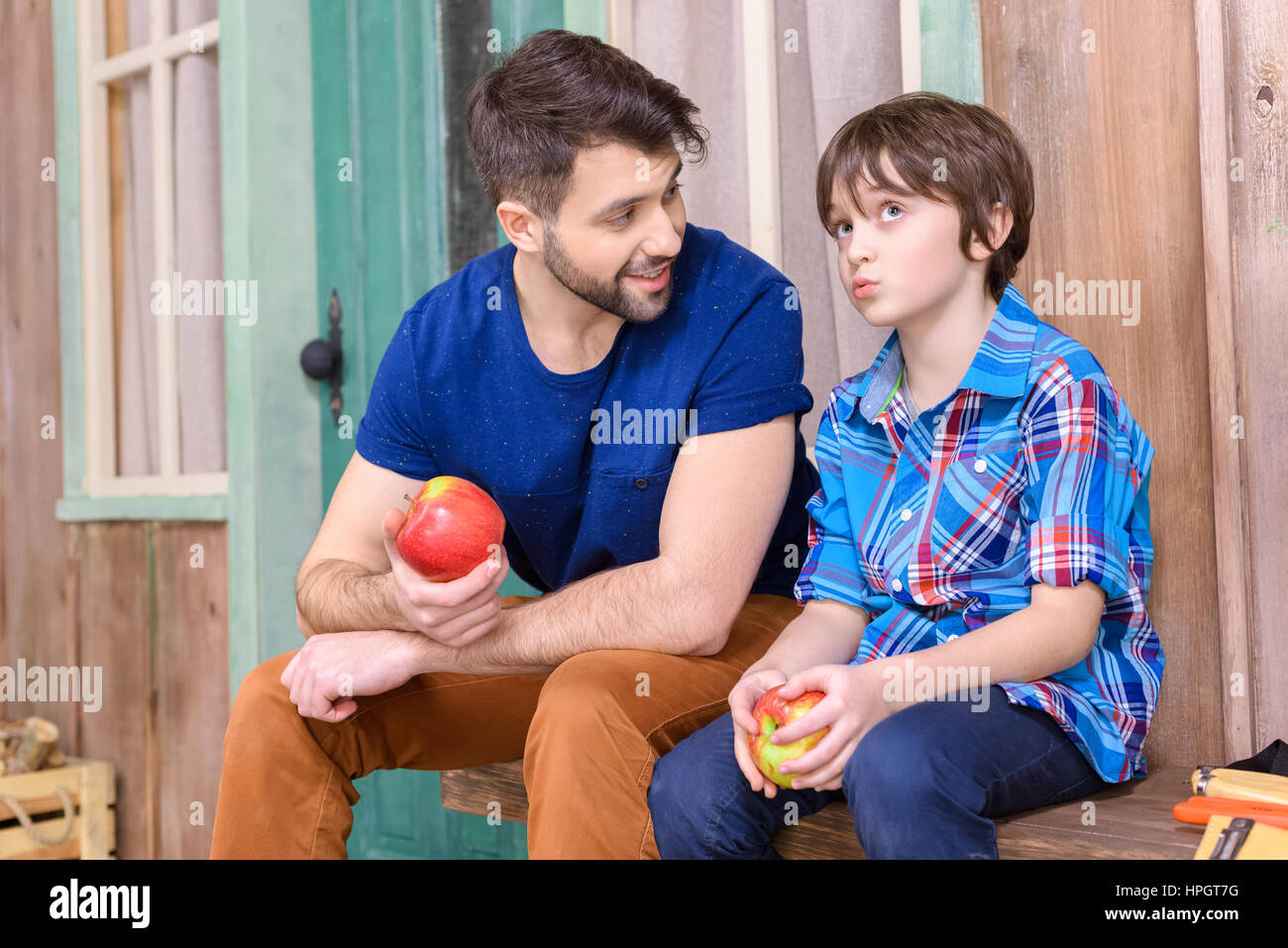 father and cute pensive son sitting on wooden bench and eating apples - Stock Image