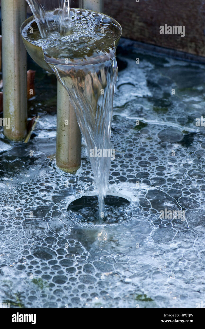 Water feature in a garden pond cascading water through a hole in the ice with bubbles forming underneath - Stock Image
