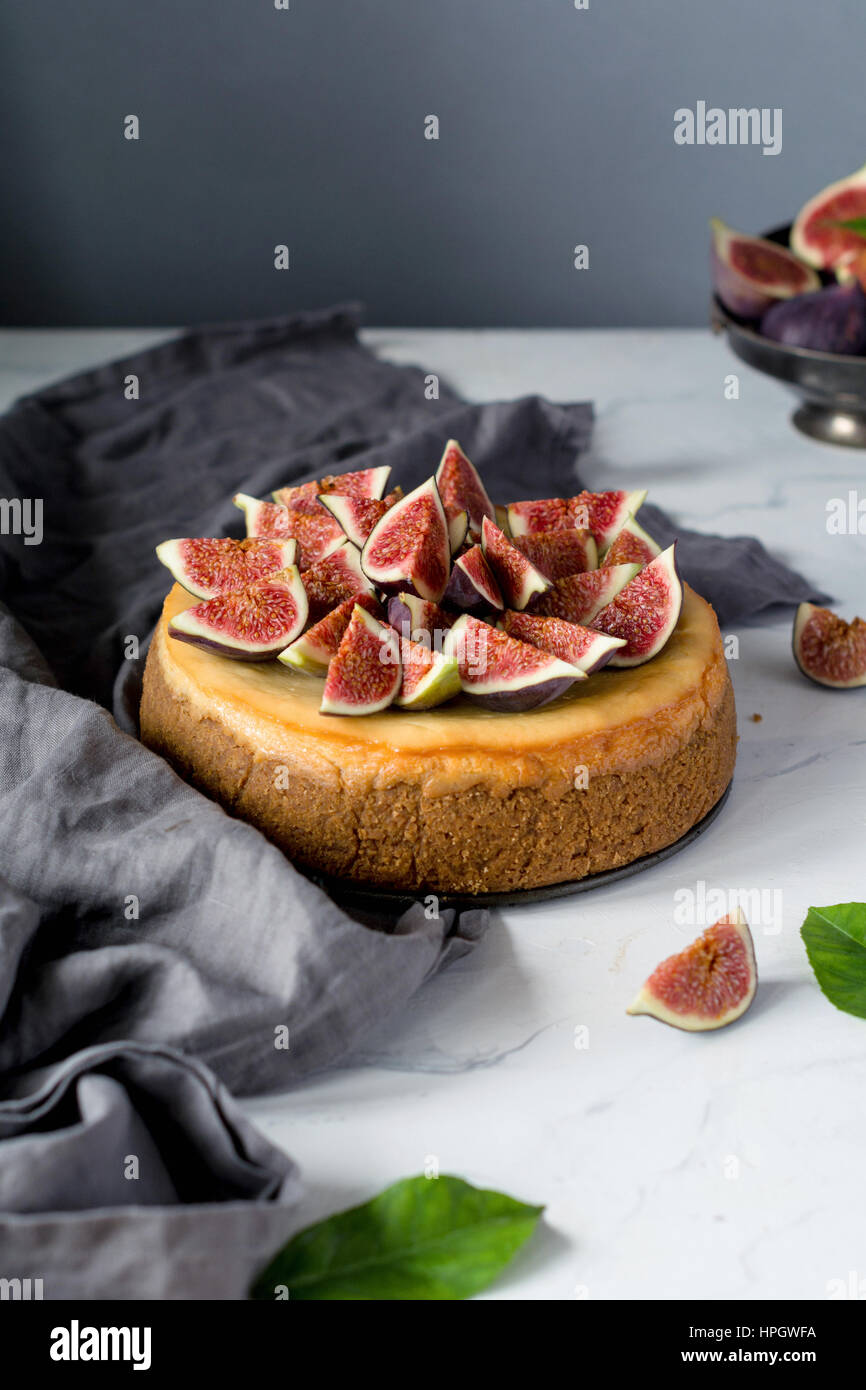 Whole cheesecake decorated with fresh figs on a marble table. Vertical view, copy space for text - Stock Image