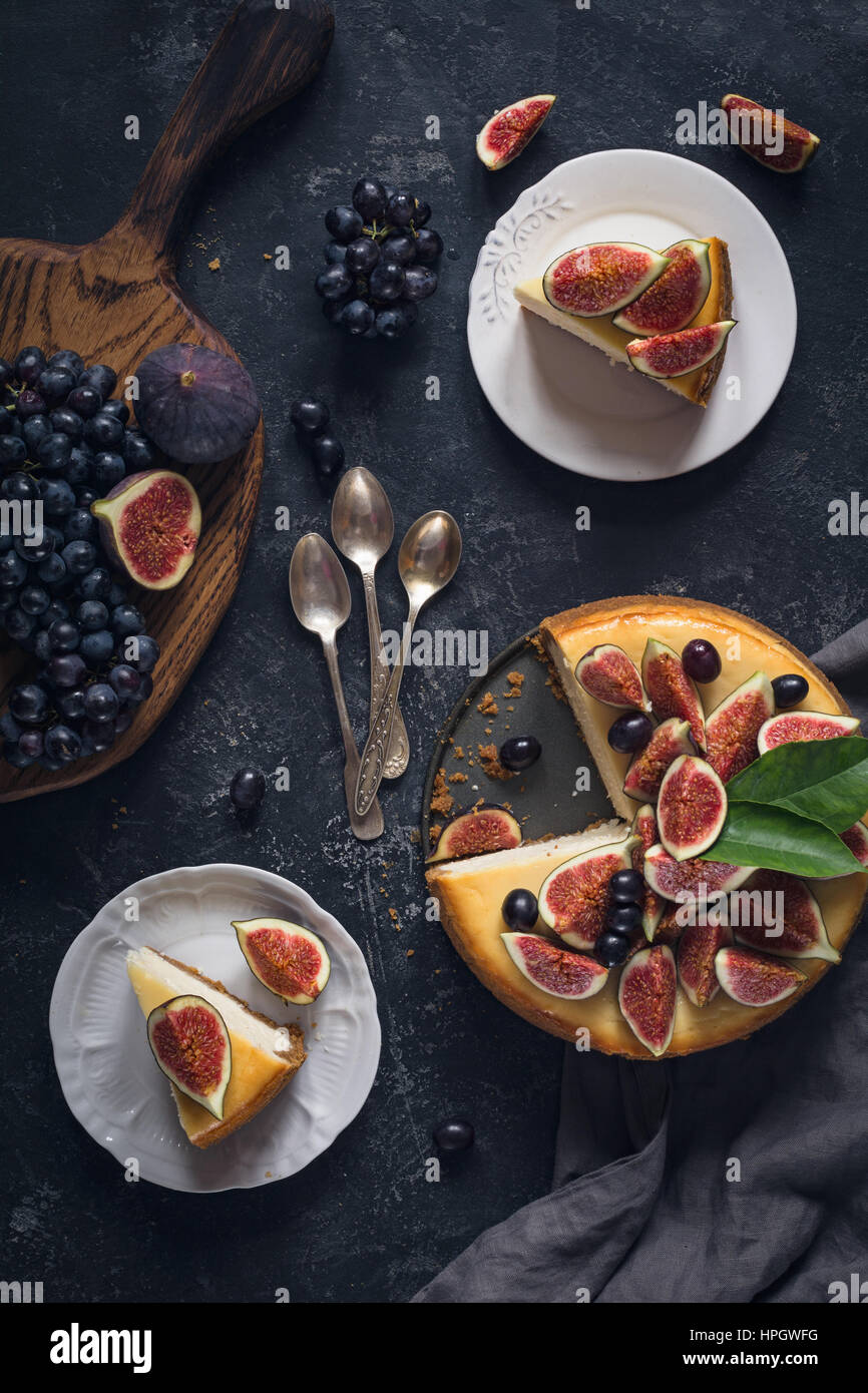 Cheesecake decorated with fresh fruits (figs and grapes). Top view, flat lay. Food still life - Stock Image