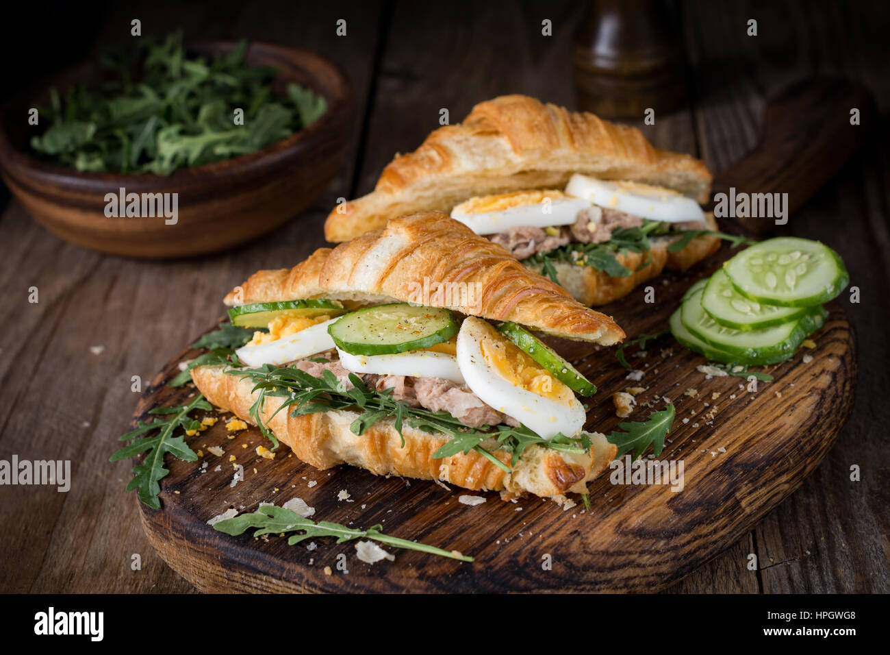Tuna croissant sandwiches on wooden cutting board. Fresh tasty tuna salad sandwiches. - Stock Image