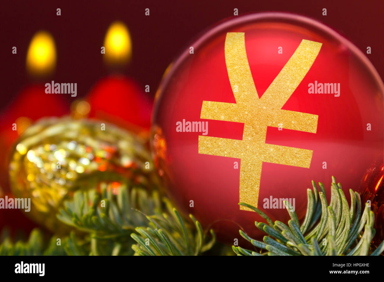 A glossy red bauble with the golden shape of a Yen symbol.(series) - Stock Image