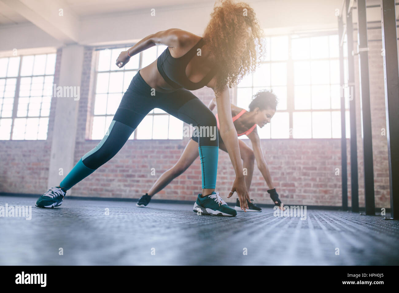 Shot of young females running in the gym. Women doing fitness workout in healthclub. - Stock Image