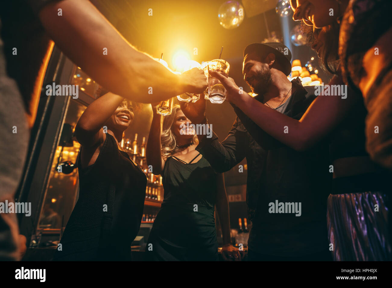 Low angle shot of group of friends enjoying drinks at bar together. Young people at nightclub toasting cocktails. - Stock Image