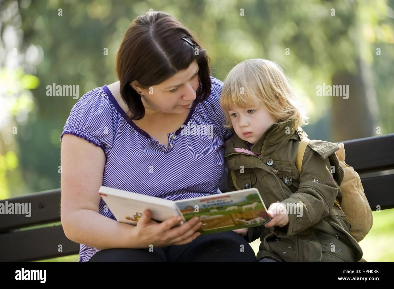 Model released , Mutter und Tochter, 3, sitzen auf einer Bank und betrachten ein Bilderbuch - mother and daughter - Stock Image