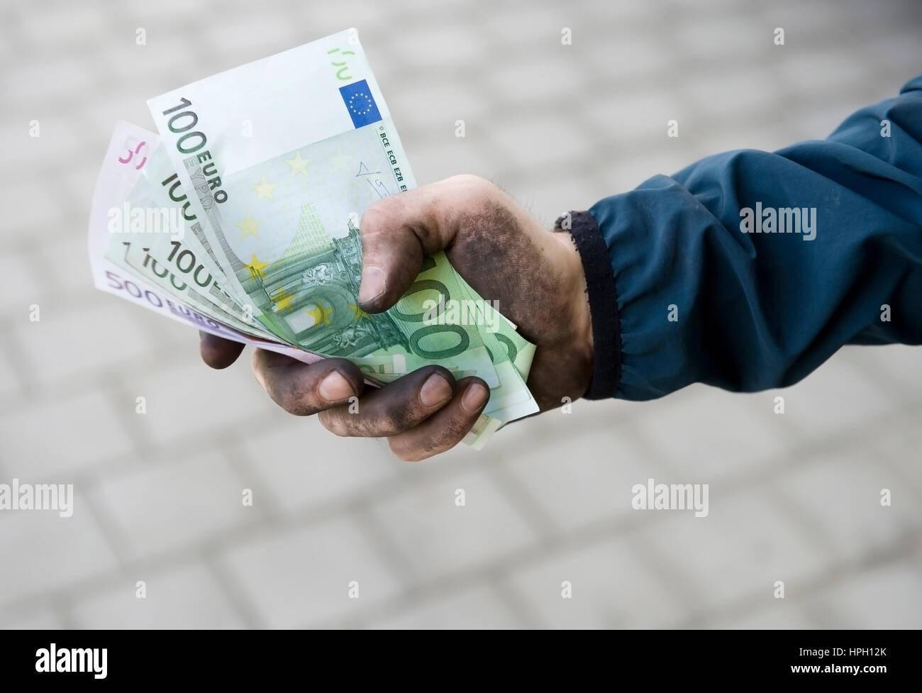 Model released , Symbolbild Schwarzgeld, Arbeiter mit schmutzigen Haenden haelt Geldscheine - symbolic for black Stock Photo