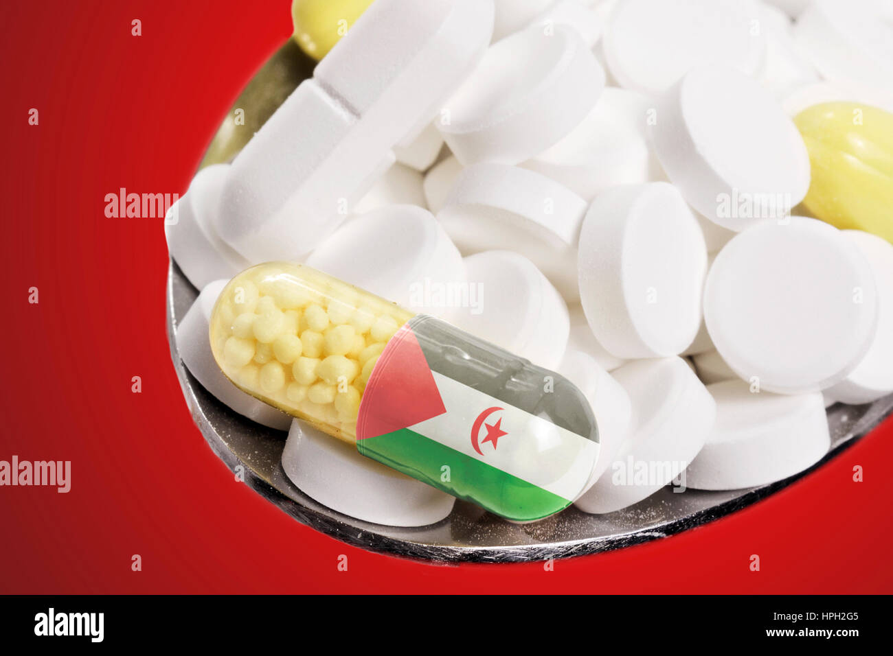 The national flag of Western Sahara on a capsule and pills on a spoon.(series) - Stock Image