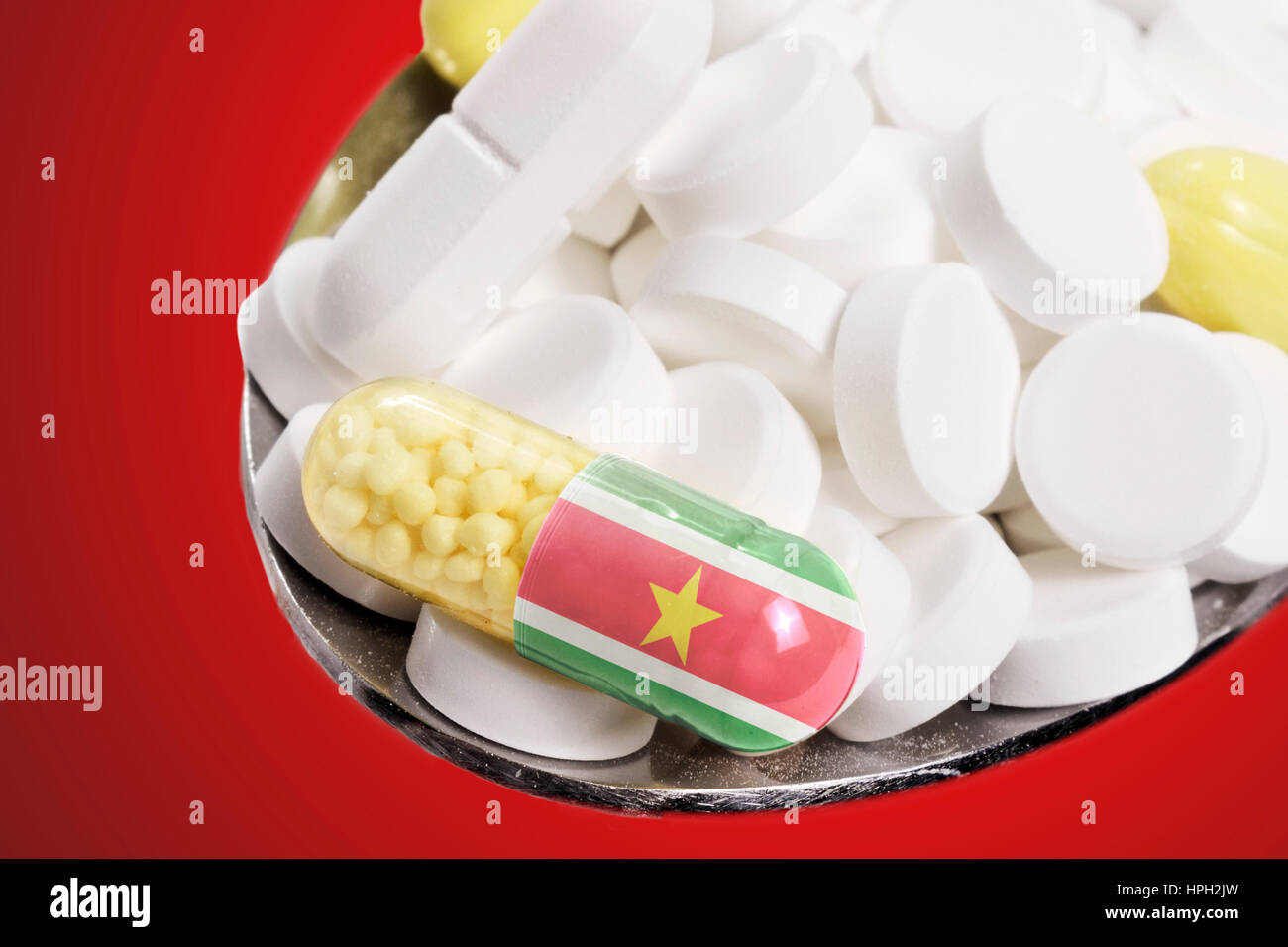 The national flag of Suriname on a capsule and pills on a spoon.(series) - Stock Image