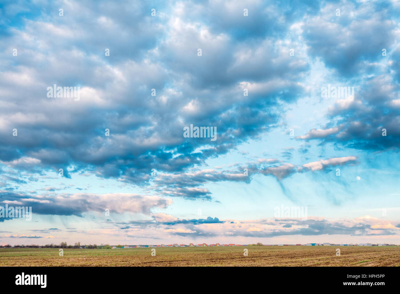 Countryside Rural Field Landscape Under Scenic Spring Blue Dramatic Sky With White Fluffy Clouds. Skyline. Agricultural - Stock Image