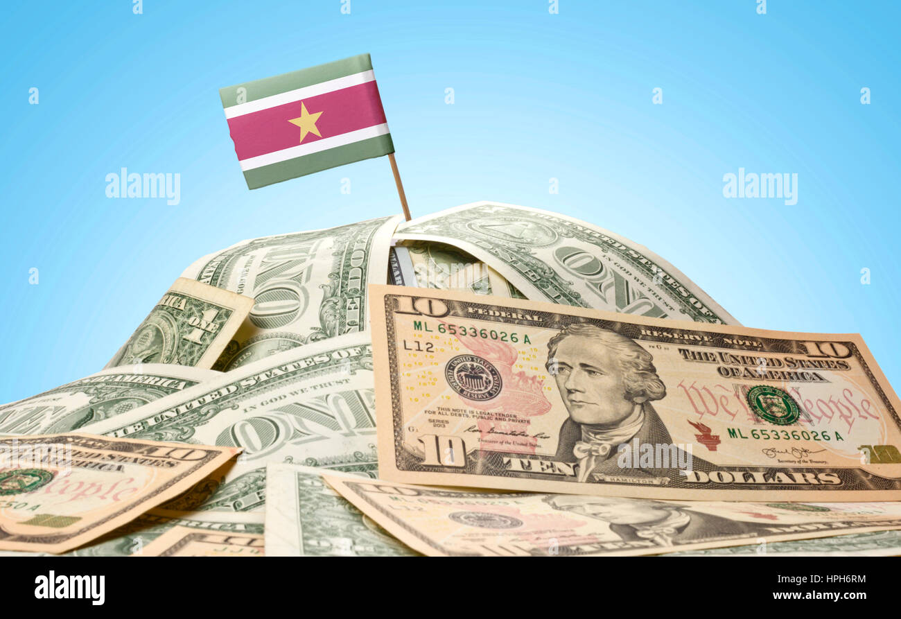 The national flag of Suriname sticking in a pile of american dollars.(series) - Stock Image