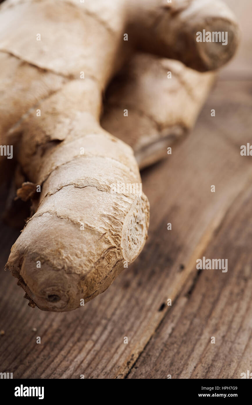 Fresh ginger root on a rustic wooden table, cooking and seasoning concept - Stock Image