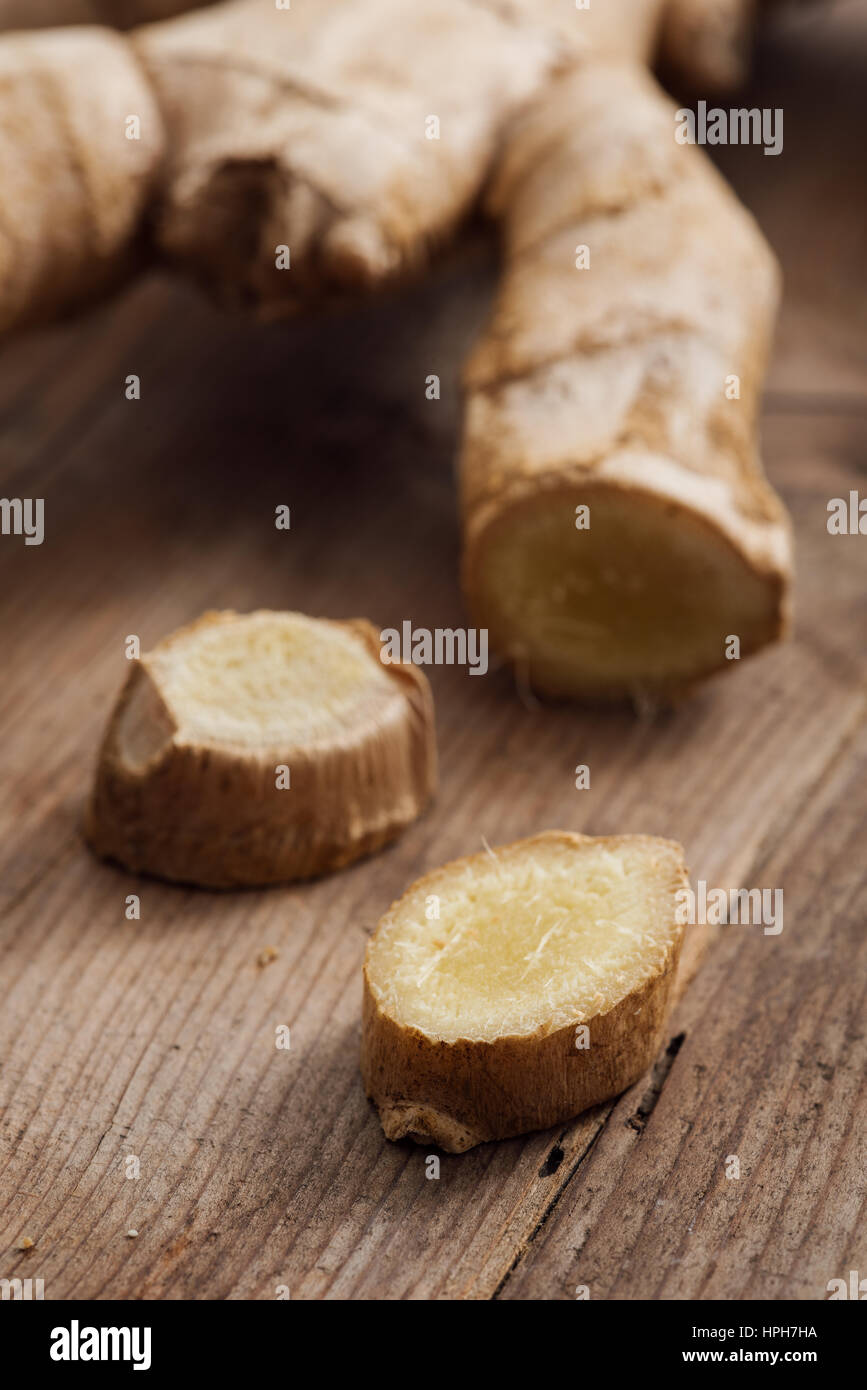 Fresh sliced ginger root on a rustic wooden table, cooking and seasoning concept - Stock Image