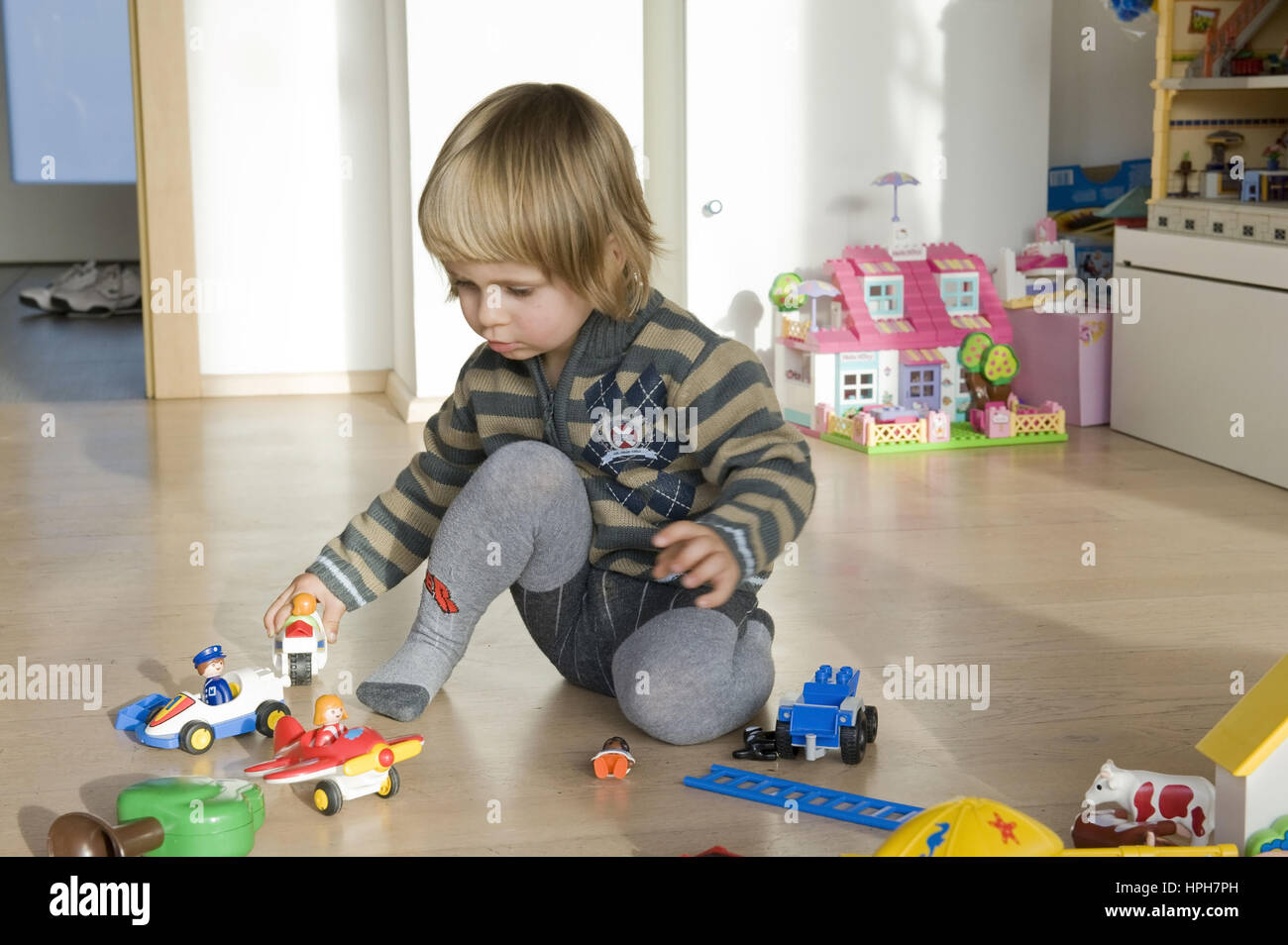 Kind spielt mirt Spielzeug am Fussboden - child playing with toys, Model released Stock Photo