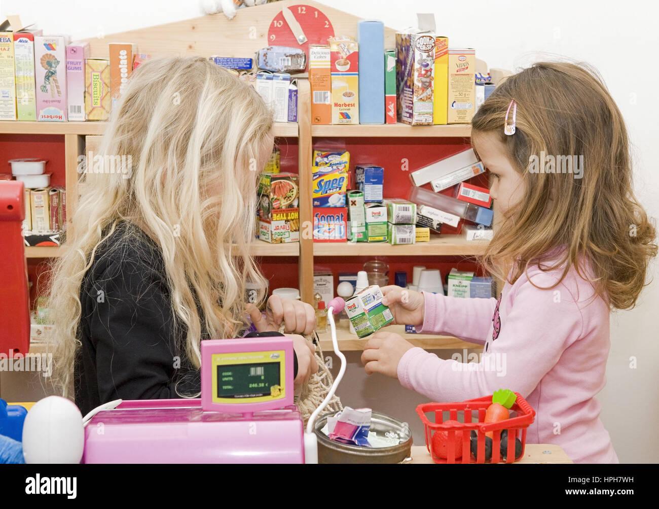 Zwei Maedchen spielen Kaufmannsladen - girls playing toy shop, Model released Stock Photo