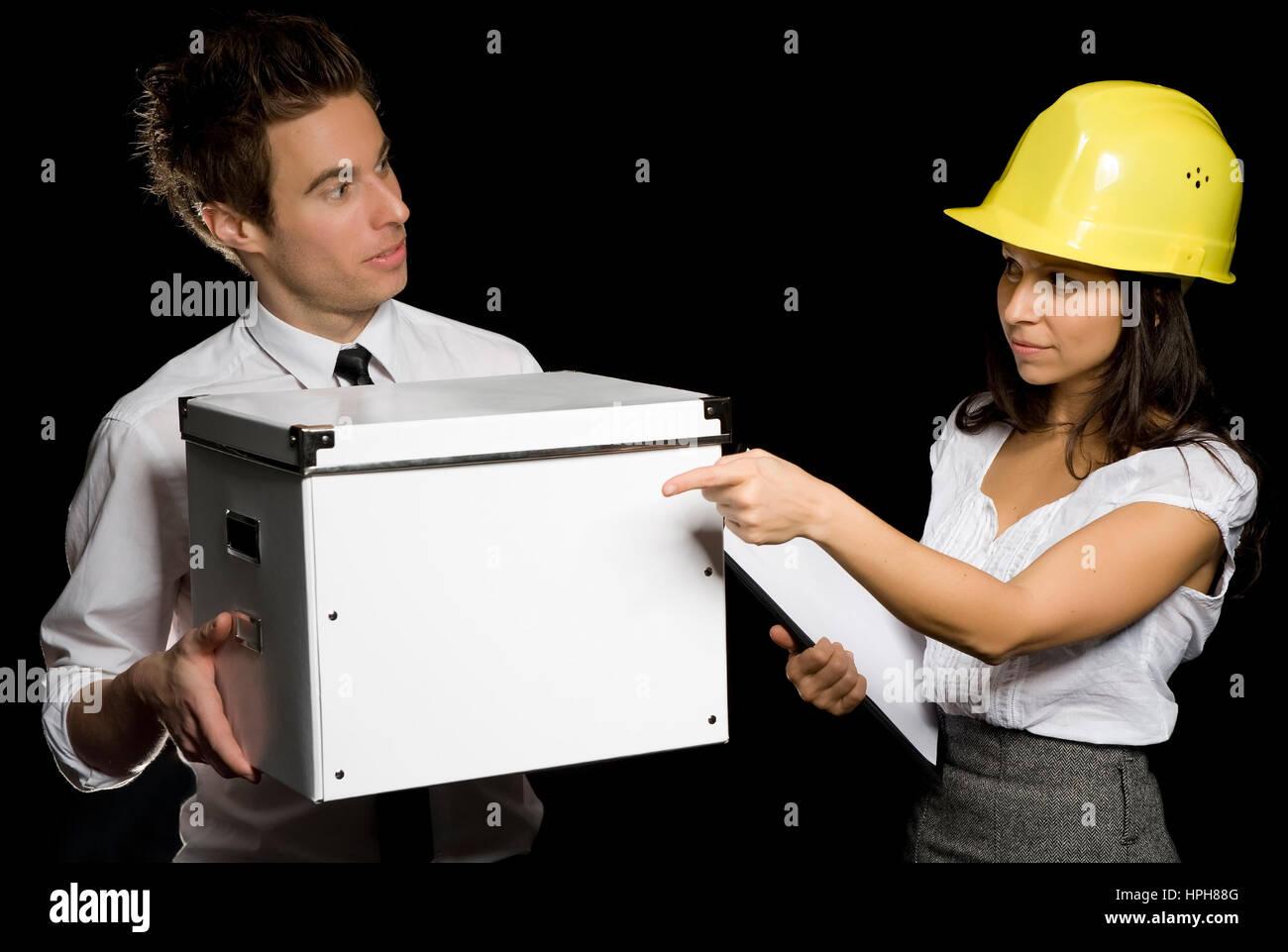 Geschaeftsfrau mit Bauarbeiterhelm deligiert geschaeftsmann - businesspeople, Model released - Stock Image