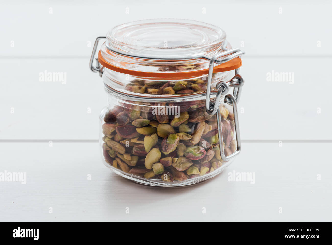 Roasted salted pistachios in a glass jar with lid - Stock Image