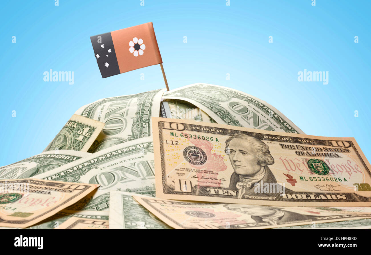 The national flag of Northern Territory sticking in a pile of american dollars.(series) Stock Photo
