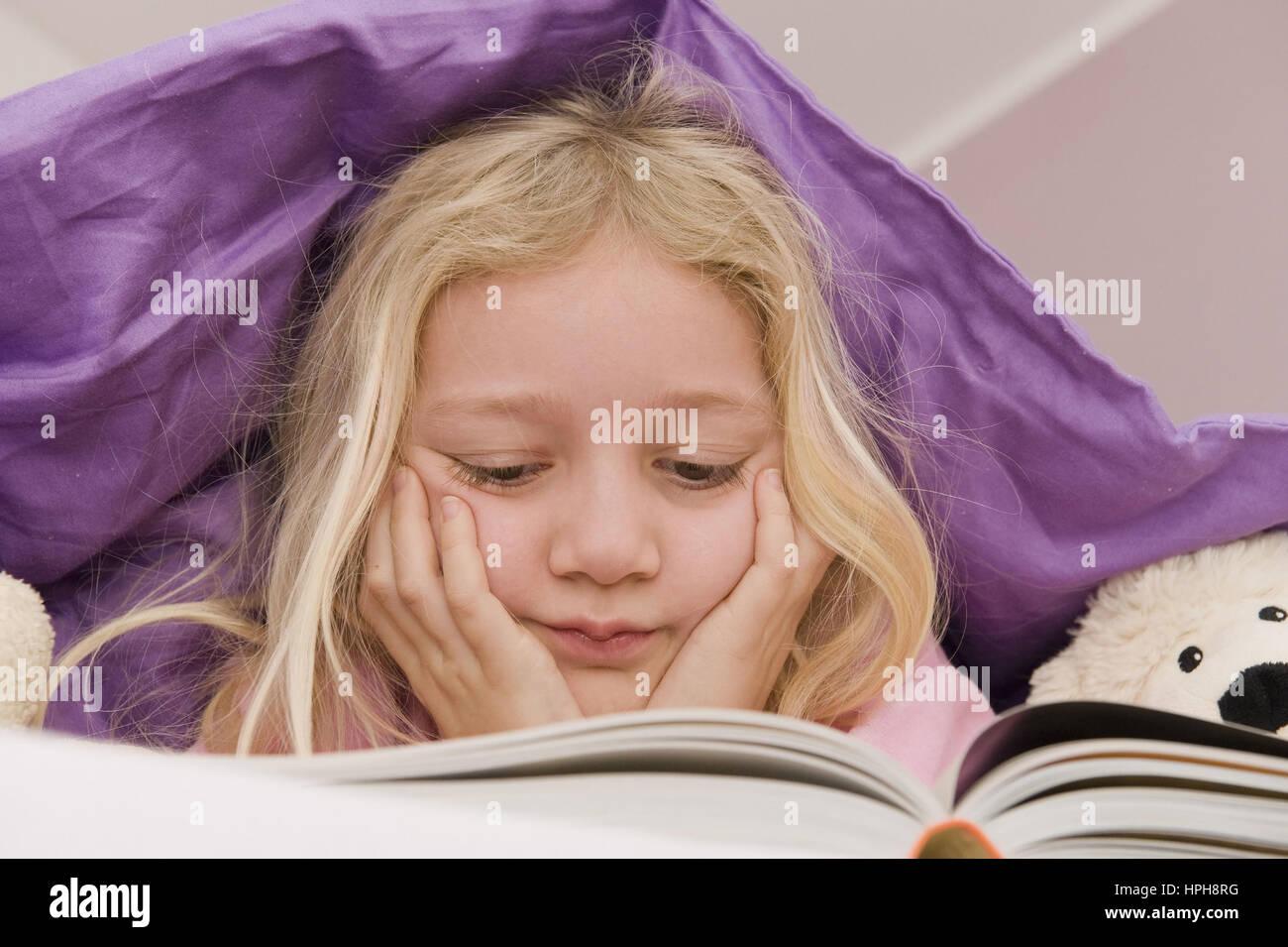 Maedchen liegt unter der Bettdecke und liest ein Buch - girl lying under bed cover reading a book, Model released Stock Photo