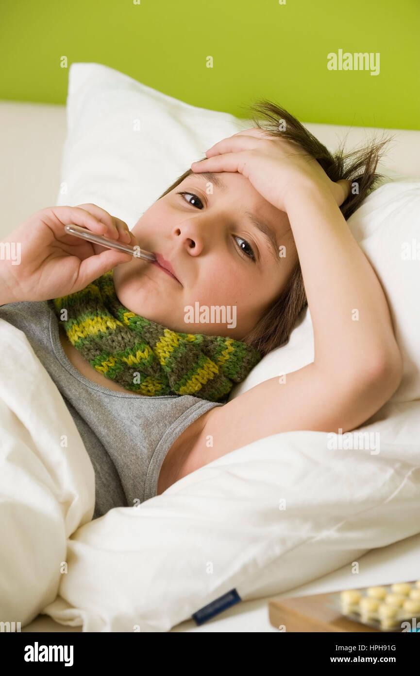 Kranker Junge mit Fieberthermometer im Bett - sick boy with fiver in bed, Model released - Stock Image