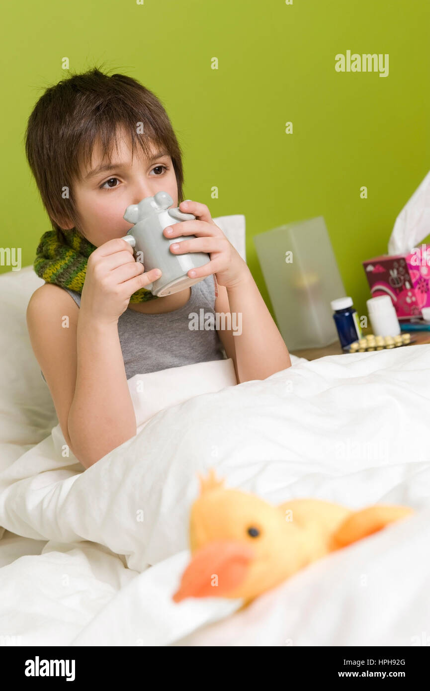 Kranker Junge mit Tasse Tee im Bett - sick boy with cup of tea in bed, Model released Stock Photo