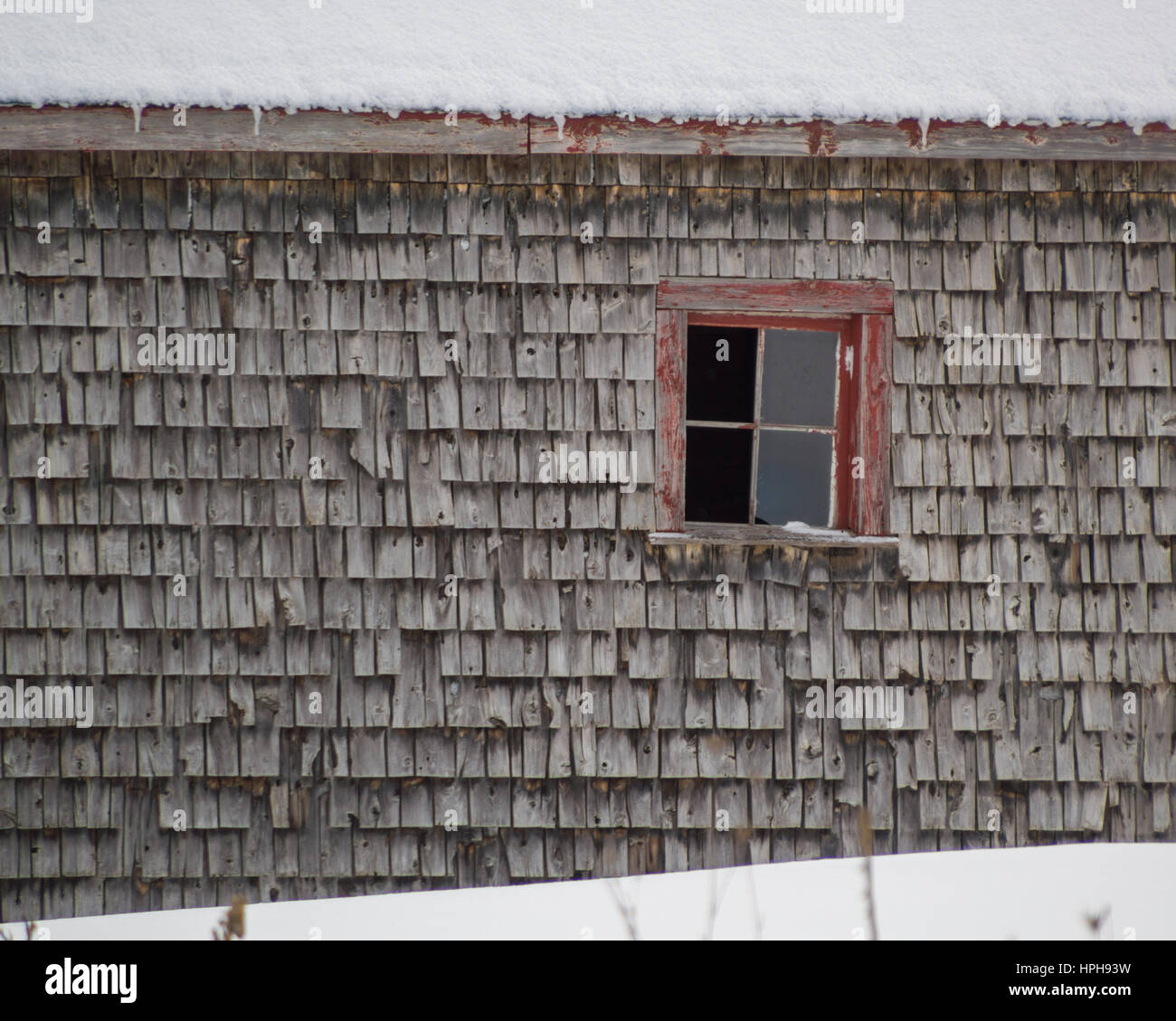 Old Weathered Cedar Shakes Shingles Barn With Red Window Winter Snow On The Roof And Ground