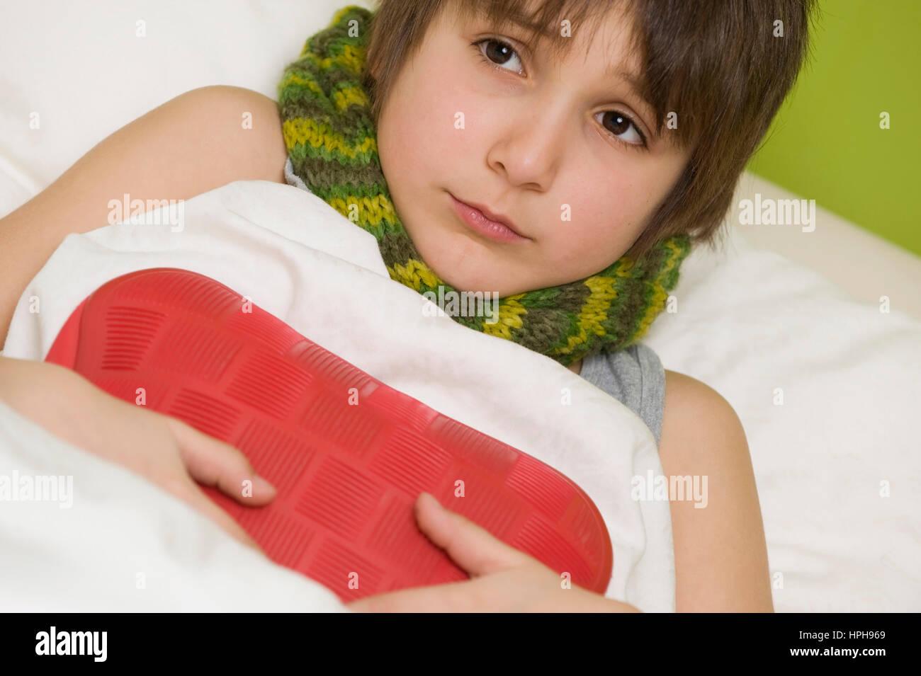 Kranker Junge mit Waermeflasche im Bett - sick boy with hot-water bottle in bed, Model released - Stock Image