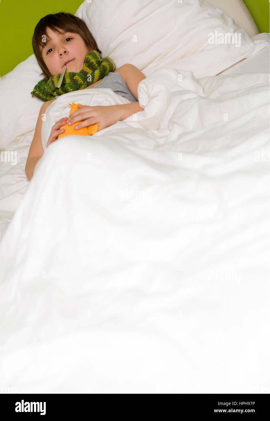 Kranker Junge liegt im Bett - sick boy in bed, Model released Stock Photo
