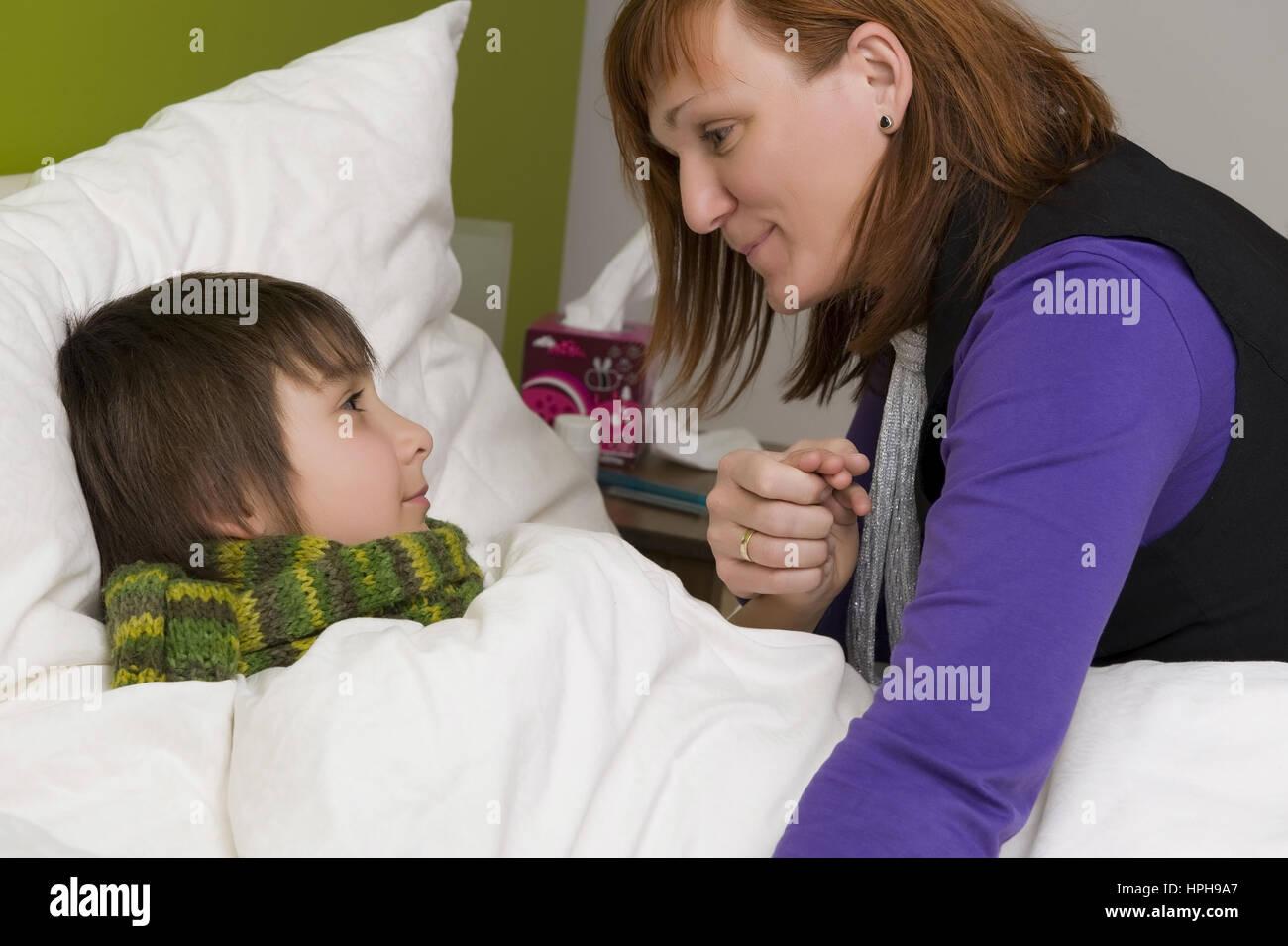 Mutter sitzt am Bett von krankem Sohn - sick son in bed, Model released Stock Photo