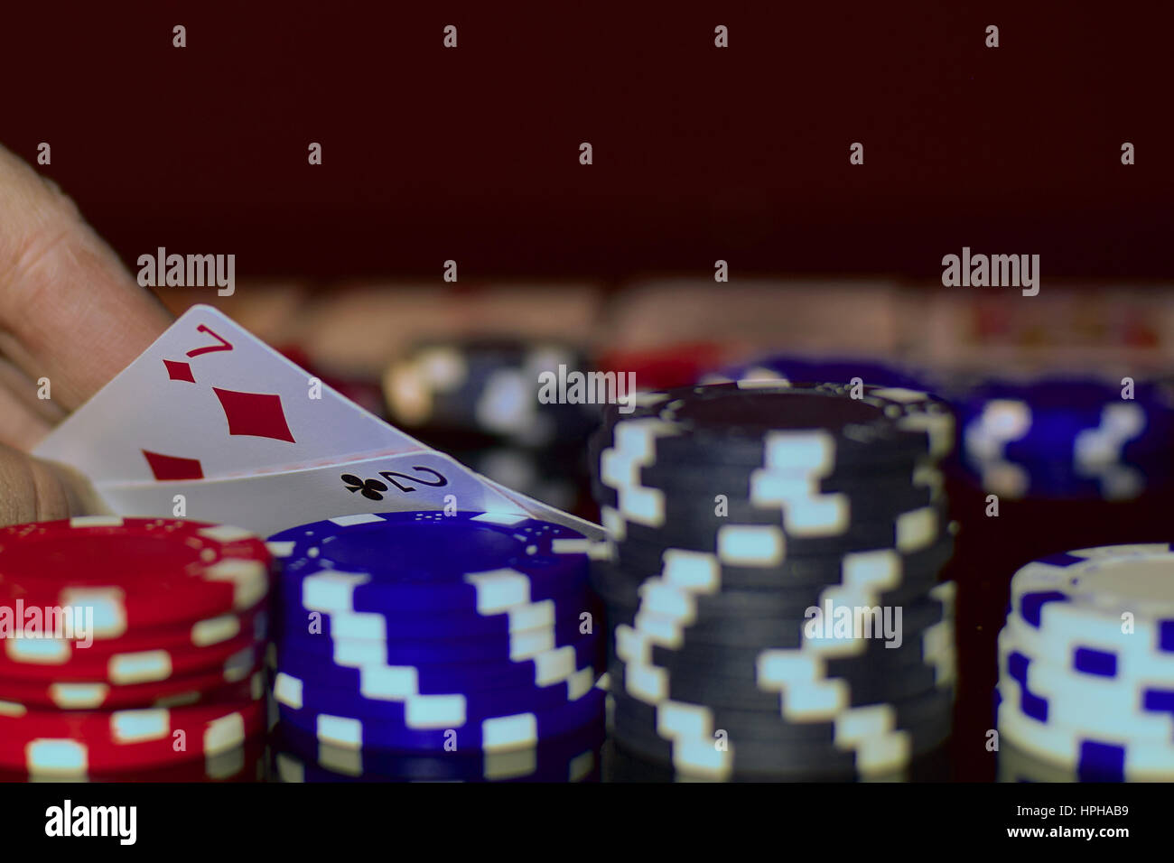 Bluffing in Texas hold'em. Poker player has very bad pocket cards. - Stock Image